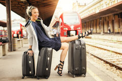 Happy woman lies on suitcases and listen music at the railway st Stock Photography