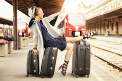 Happy woman lies on suitcases and listen music at the railway st Royalty Free Stock Photography
