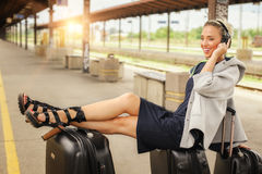 Happy woman lies on suitcases and listen music at the railway st Royalty Free Stock Image