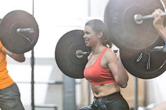 Happy woman lifting barbell in crossfit gym Stock Images