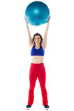 Happy woman lifting pilates ball upwards Stock Photos