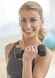 Happy Woman Lifting Weights At Gym stock image