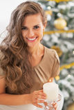 Happy woman lighting candle near christmas tree Stock Photo