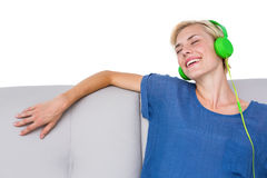 Happy woman listening music on the couch Royalty Free Stock Photos
