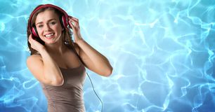 Happy woman listening music on headphones against reflection of sunlight in water. Digital composite of Happy woman listening music on headphones against Royalty Free Stock Photos