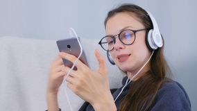 Happy woman is listening music in headphones on smartphone conducting by hands and singing a song. Happy woman is listening music in headphones on smartphone stock video