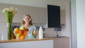 Happy woman listening music with smartphone in kitchen. Happy girl stock video