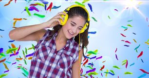 Happy woman listening to music against colorful feathers Royalty Free Stock Image