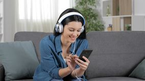 Happy woman listening to music from cell phone. Sitting on a couch at home stock video footage