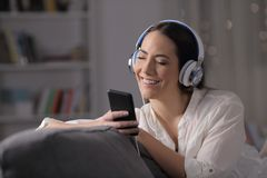 Happy woman listening to music feeling well at home stock photo