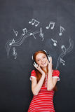 Happy woman listening to music in headphones over blackboard background Royalty Free Stock Image