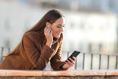 Free Happy Woman Listening To Music Putting Earbuds Stock Image - 164500851