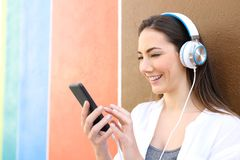 Happy woman listening to music using phone outdoors royalty free stock images
