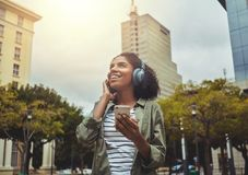 Happy woman listening to music wearing headphones. Wide shot of a smiling young woman holding smart phone in hand enjoying music on wireless headphones in the royalty free stock image
