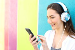 Happy woman listens to music in a colorful street royalty free stock photography