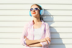 Happy woman listens to music in headphones over white Royalty Free Stock Photos