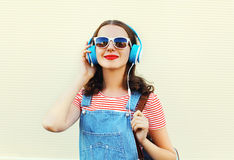 Happy woman listens to music in headphones over white Royalty Free Stock Photo