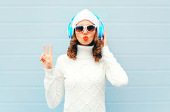 Happy woman listens to music in headphones wearing a sunglasses, knitted hat, sweater over blue background, blowing lips Royalty Free Stock Photos