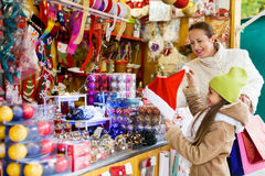 Happy woman with little daughter buying gifts at Christmas mark Royalty Free Stock Photo