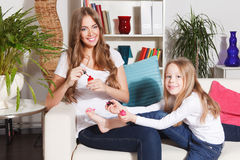 Happy woman and little girl putting nail polish on Royalty Free Stock Photos