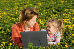 Happy woman and little girl relaxing outdoors Stock Image