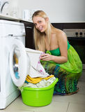 Happy  woman loading clothes into washing machine Stock Image