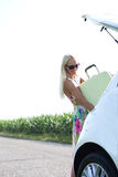 Happy woman loading suitcase in car trunk against clear sky Royalty Free Stock Photo