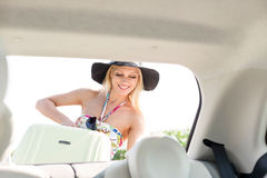 Happy woman loading suitcase in car trunk Stock Image