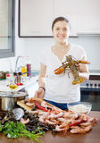 Happy woman with lobster   in home kitchen. Happy woman with lobster and other seafood  in home kitchen Royalty Free Stock Image