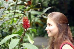 Happy woman loking at exotic flower. At garden Royalty Free Stock Image