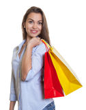 Happy woman with long dark hair and shopping bags Stock Images