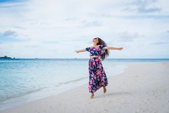 Happy woman with raised hands on beach with transparent ocean water in Maldives