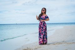 Happy woman in long dress shows thumb up on beach in Maldives. Happy woman in long dress shows thumb up on beach with pure water in Maldives Royalty Free Stock Photo