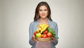 Happy woman with long hair and big toothy smile holding straw ba. Sket with healthy food fruits and vegetables Stock Images