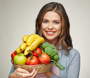 Happy woman with long hair and big toothy smile holding straw ba. Sket with healthy food fruits and vegetables Royalty Free Stock Images