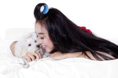 Happy woman with long hair and dog on bed. Picture of cheerful pretty woman with long hair smiling happy while hugging a maltese dog on the bed Royalty Free Stock Photography