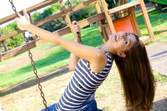 Happy woman with long hair swinging in park Royalty Free Stock Photos