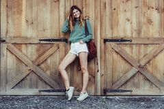 Happy woman with long legs look to the side near barn on the farm wearing casual outfit with shorts, backpack and sneakers. Happy woman with long legs look to stock photo