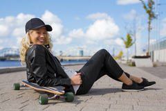 Happy woman with longboard sitting on the ground Stock Photo