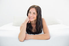 Happy woman looking away in bed Royalty Free Stock Photo