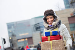 Happy woman looking away while carrying stacked gifts during winter Stock Photo
