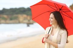 Happy woman looking away holding a red umbrella outdoors. On the beach royalty free stock image