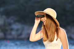 Happy woman looking through a binoculars on the beach. With the sea in the background Stock Photography