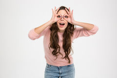 Happy woman looking at camera through fingers Stock Image