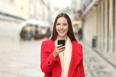 Happy woman looking at camera holding a phone in winter. Happy woman in red looking at camera holding a phone in winter in the street royalty free stock images