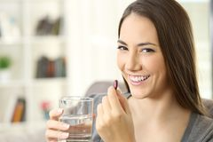 Happy woman looking at camera holding a pill Royalty Free Stock Image
