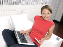 Happy woman looking at camera with laptop. An attractive happy woman purchasing product online using her laptop computer Royalty Free Stock Photography