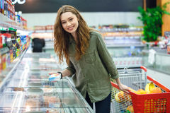 Happy woman looking camera in mall. Happy woman buying products with cart looking camera in mall Stock Image