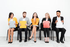 Happy woman looking at camera in office. Photo of a happy women looking at camera while her confused colleagues sitting in office looking at her Stock Image