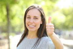 Happy woman looking at camera with thumbs up in a park. Happy woman looking at camera with thumbs up standing outdoors in a park royalty free stock photos